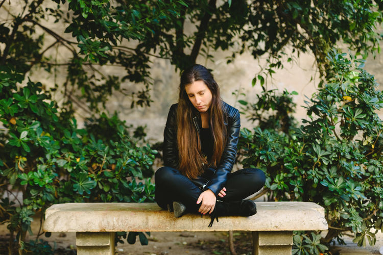 Portrait of young woman sitting on tree against plants