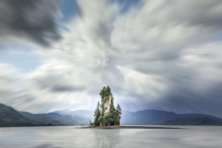 Rock formations amidst sea against cloudy sky