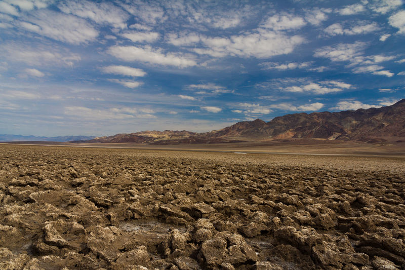 Devils Golf Course Death Valley Desert Rock Formation Transportation Arid Climate Beauty In Nature Blue Sky And White Clouds Cloud - Sky Day Desert Devils Golf Course Dune Horizon Over Land Landscape Lonely Road Mountain Mountain Range Nature No People Outdoors Physical Geography Scenics Sky Tranquility EyeEmNewHere Lost In The Landscape