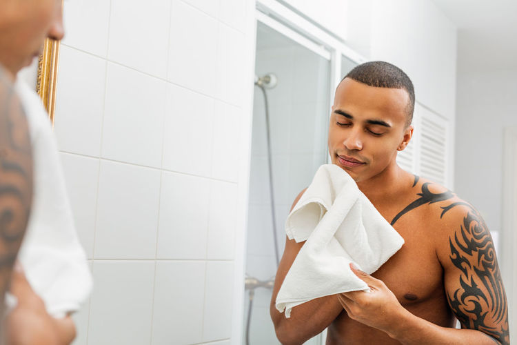 Bathroom Indoors  Home One Person Lifestyles Real People Standing Shaving Cream Shaving Towel Indoors  Looking Reflection Mirror Skin Care Hygiene Body Care Bare Chest