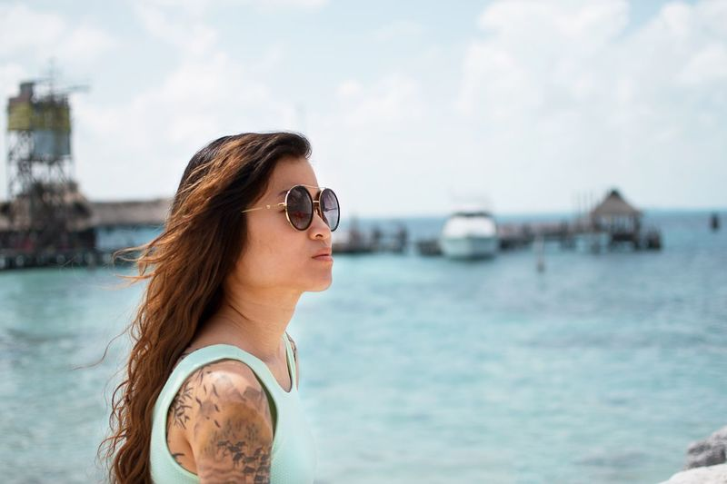 Young Woman Wearing Sunglasses By Sea Against Sky