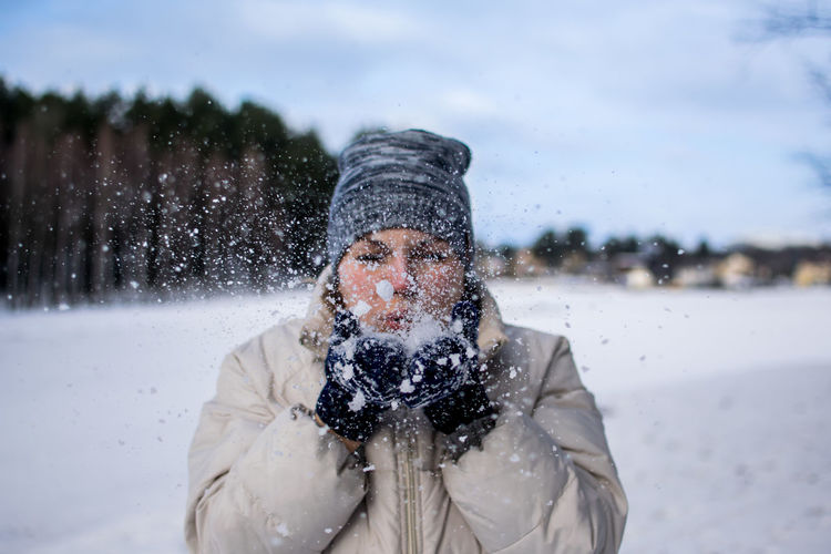 Adult Blowing Snow Cold Temperature Day Front View Motion One Person Outdoors Particles People Snow Happyness warm clothing White Winter Woman Shades Of Winter