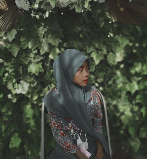 Young woman looking away while standing against trees