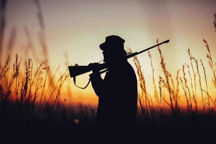 Man Holding Gun At Sunset