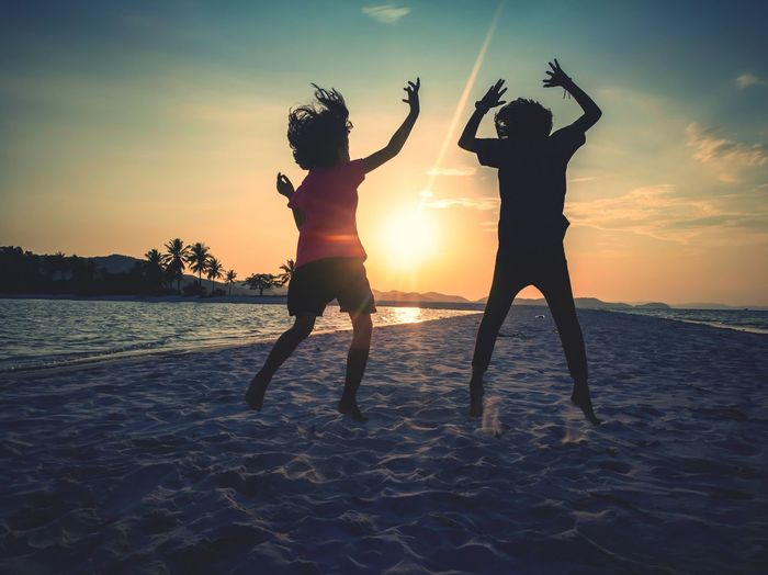 Silhouette girls jumping at beach against sky during sunset