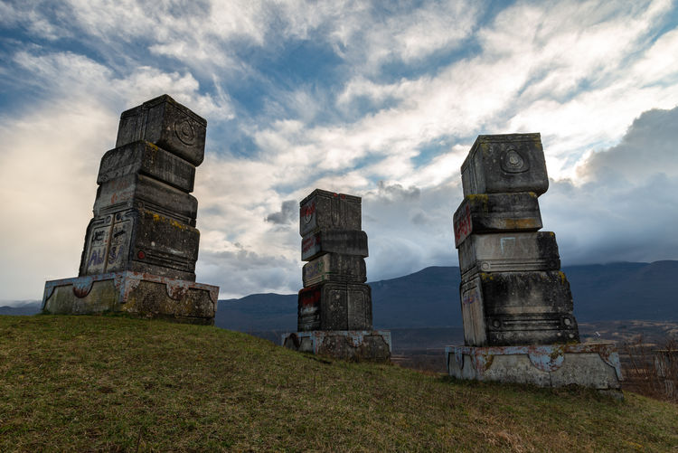 Low angle view of old ruins on field against sky