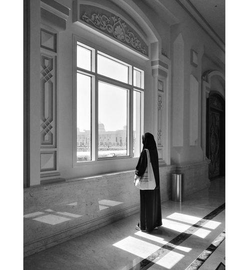 Rear view of woman standing by window in building