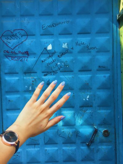 Person hand against blue wall
