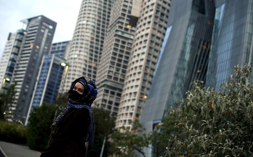Low angle view of woman standing against modern buildings