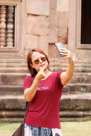 Woman taking selfie through mobile phone against building