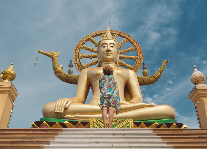 Low angle view of woman standing by buddha statue at temple against sky
