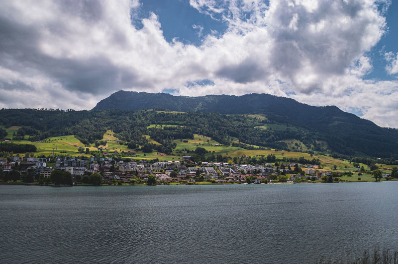 Scenic view of town by lake against sky