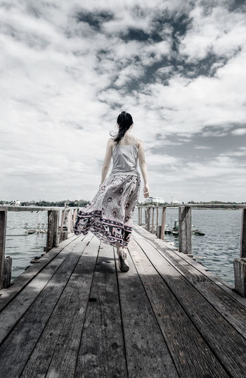 Cloud - Sky Cloudy Day Full Length One Person One Woman Only One Young Woman Only Outdoors People Pier Rear View Shade Skirt Sky Sleeveless Top Summer Sunny Sunny Day Travel Vacations Water Windy Day Women Wood - Material Young Adult