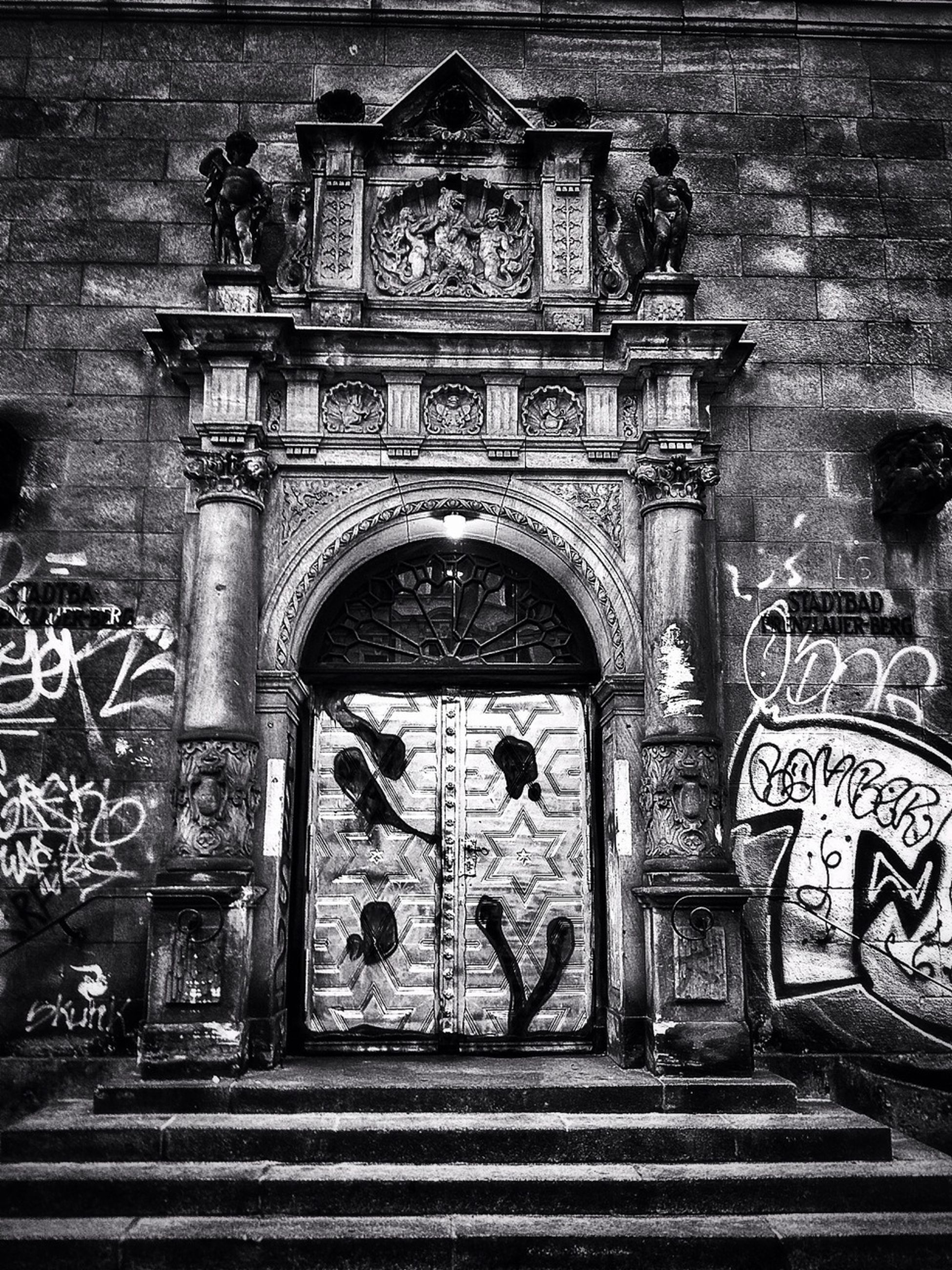 architecture, built structure, building exterior, art and craft, art, entrance, creativity, door, text, human representation, gate, graffiti, wall - building feature, facade, arch, old, outdoors, ornate, closed, day
