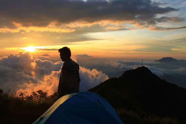 Man campint on top of a hill at sunset