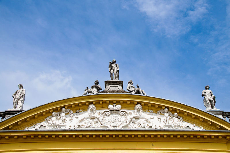 Low angle view of statues on historic building against blue sky