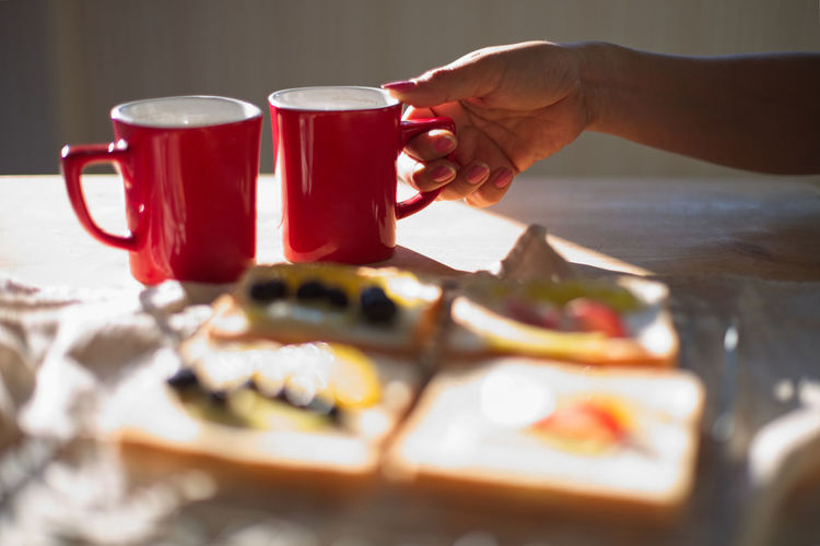 Breakfast Food And Drink Berry Fruit Bread Coffe Cup Coffee Cup Cup Drink Food Food And Drink Freshness Glass Hand Human Body Part Human Hand Indoors  Jam Lifestyles Mug One Person Preparation  Preparing Food Real People Red Refreshment Selective Focus Table Toasted Bread