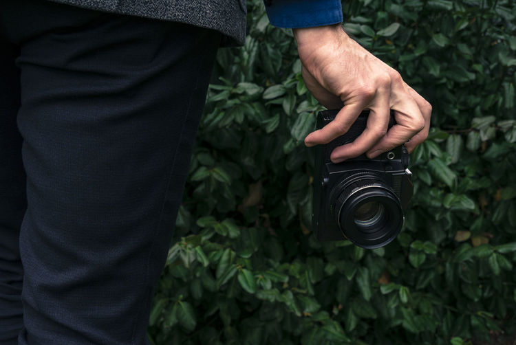 Male hand holding a vintage film camera in the air. Green nature in the background. Camera Camera - Photographic Equipment Film Plant Retro Analog Backgrounds Black Equipment Green Background Hand Holding Leaves Lens Old Outdoors Vintage Zenit Fresh On Market 2017