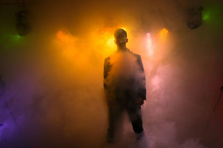Man Standing Amidst Illuminated Smoke On Stage