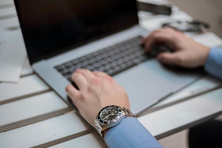 Cropped hands of businessman using laptop on desk