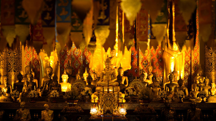 Close-up of statue against illuminated temple