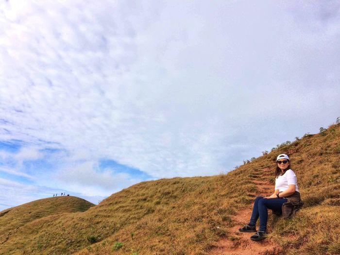 Full Length Of Woman Sitting On Land Against Sky