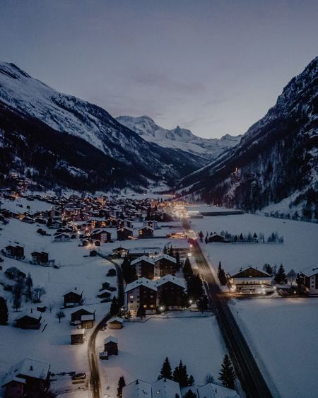 Aerial shot of town surrounded by snowcapped mountains at dusk during winter