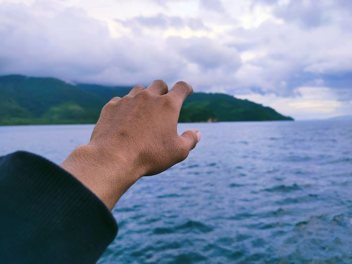 Close-up of hand against sea against sky