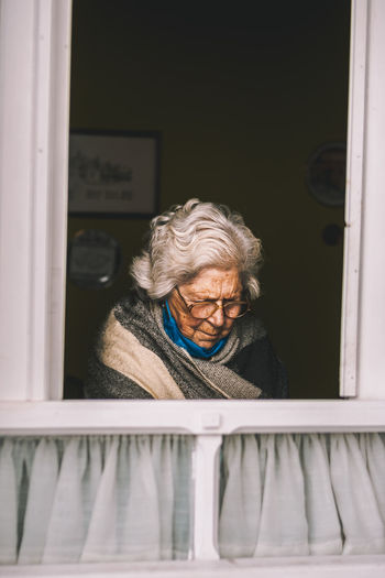 Portrait of smiling woman looking through window at home