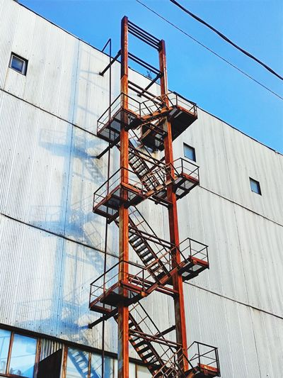Old rusty stair on industrial building facade