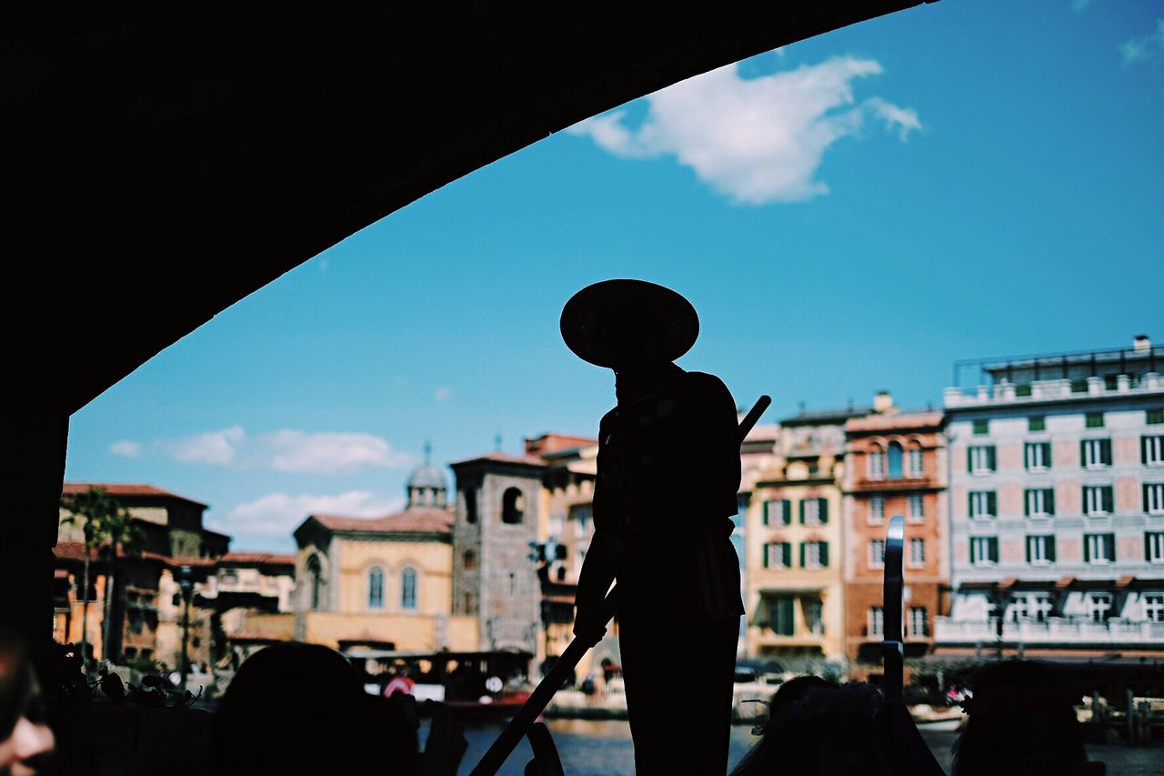 Silhouette gondolier in boat against city