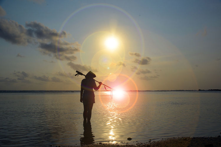 10 Beauty In Nature Horizon Over Water Lens Flare Nature One Person Orange Color Reflection Sea Silhouette Sky Standing Sun Sunset Water