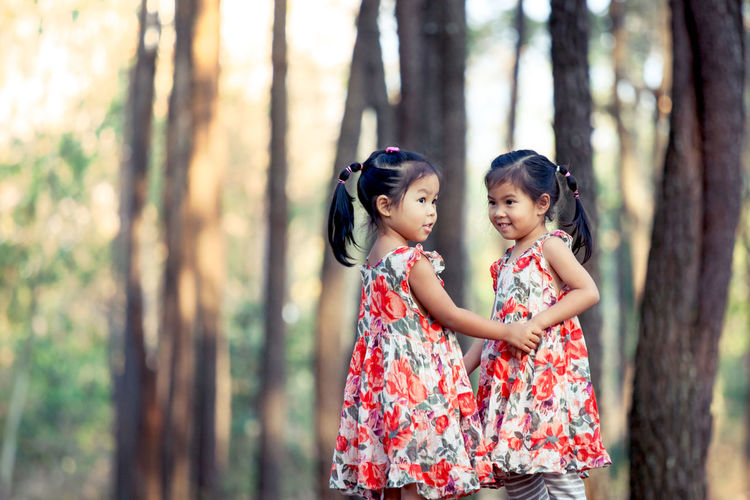 Twin sisters standing in forest
