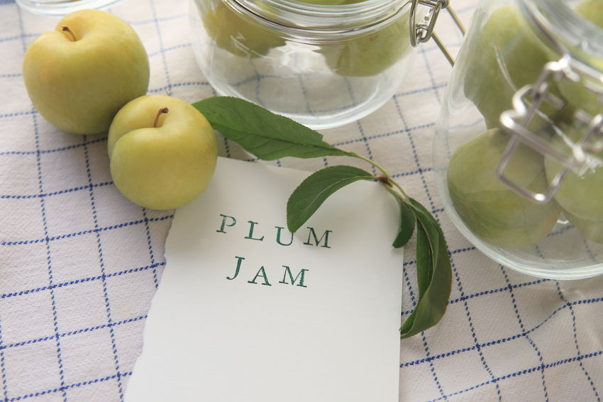 Fresh green plums with plum jam words Close-up Concert Copy Space Day Dish Towel Fabric Foliage Food Preparation Fresh Fruit Glass Jars Green Color Grid Pattern Healthy Eating High Angle View Indoors  Leaves No People Paper Preserving Ripe Summer Words