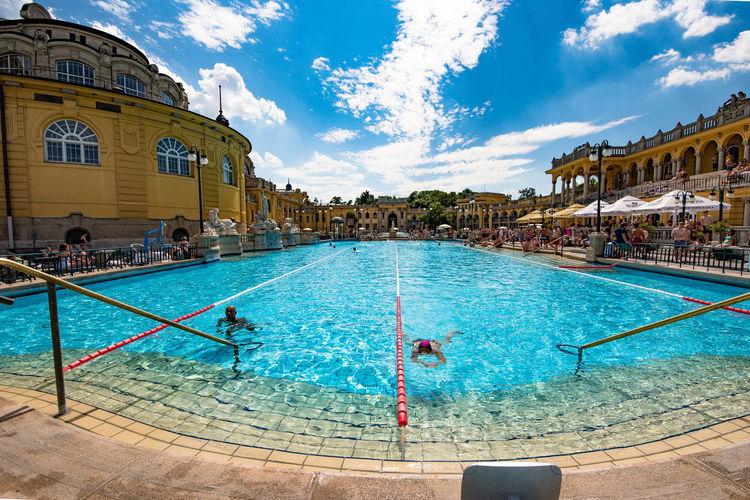 People swimming in pool against blue sky