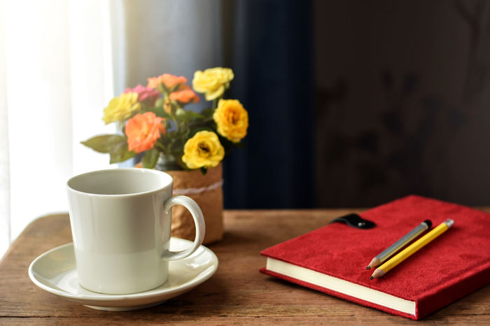 White cup of hot coffee on wooden table by the window. Small vibrant color roses and red cover notebook with pencils on it as background. Coffee Desk Americano Coffee Book Coffee - Drink Coffee Break Coffee Cup Cup Curtain Diary Drink Flower Flower Vase Food And Drink Freshness Mug Note Pad Refreshment Relaxing At Home Saucer Small Roses Table Window Window Light Working At Home