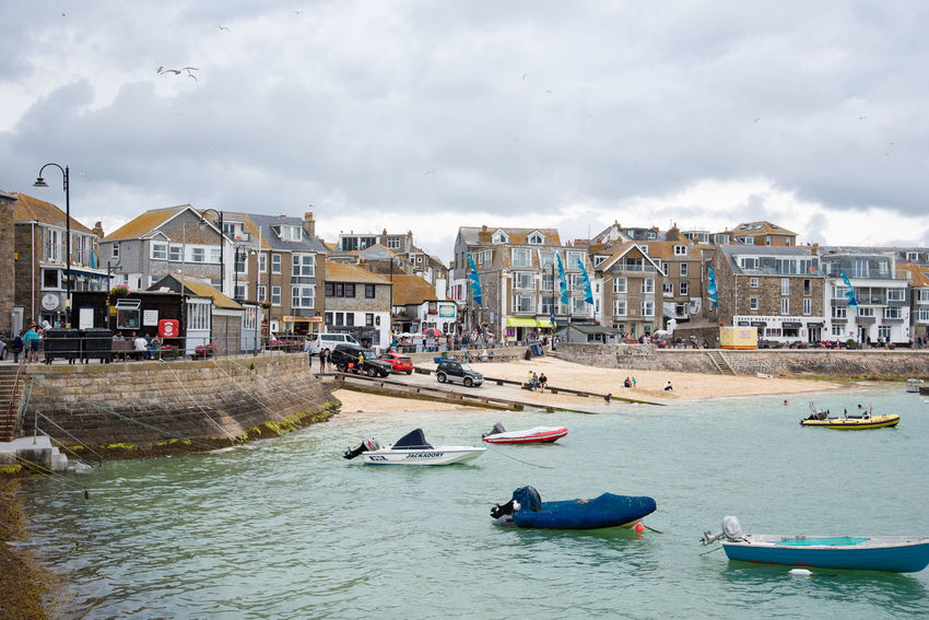 Harbour of the bustling city of St Ives. The water is brilliant green here, a good contrast to the colorful houses and the yellow beach Harbor Building Building Exterior Built Structure City Cloud - Sky Day Green Water Incidental People Nautical Vessel Outdoors Real People Residential District Sky Water