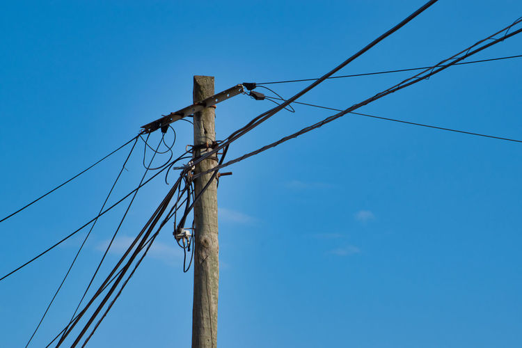 Electric wire poles Cable Connection Blue Sky Low Angle View Electricity  Power Supply Technology No People Day Nature Telephone Line Outdoors Clear Sky Electrical Equipment Power Line  Electricity Pylon Telephone Pole Pole Fuel And Power Generation Wood - Material Complexity Daylight
