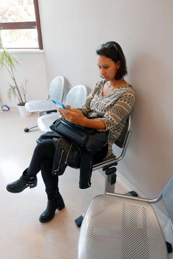 Young Woman Using Digital Tablet While Sitting On Chair At Hospital