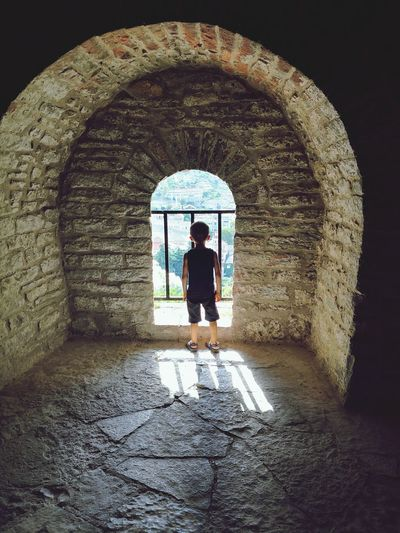 Rear view of boy standing at window of historic building