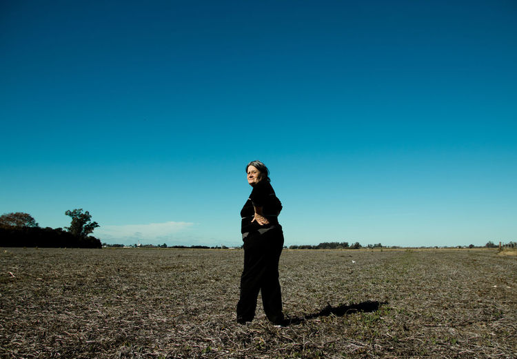 Portrait of woman standing on land against clear blue sky