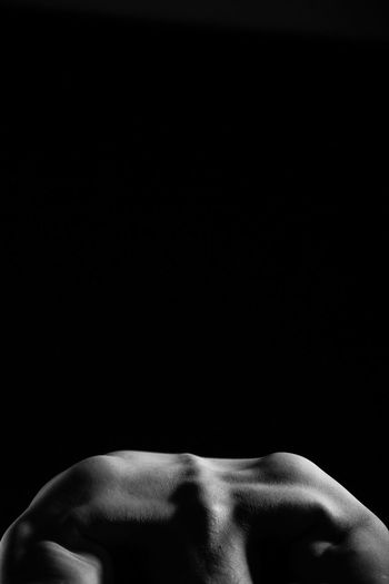 Midsection of shirtless man bending against black background