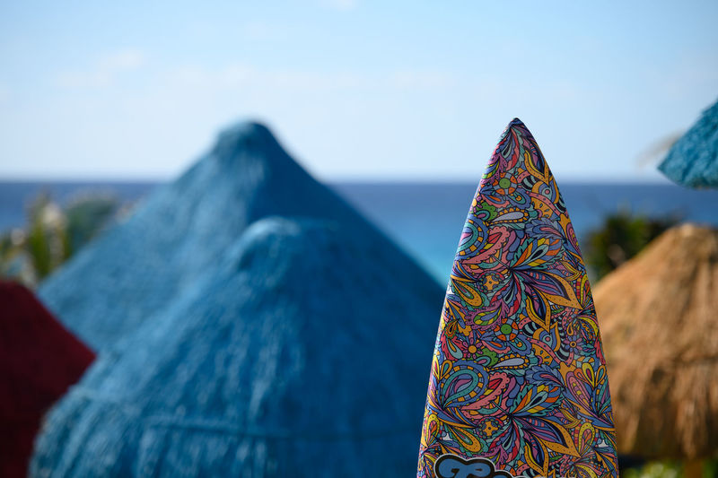 Close-up of multi colored umbrella against blue sky