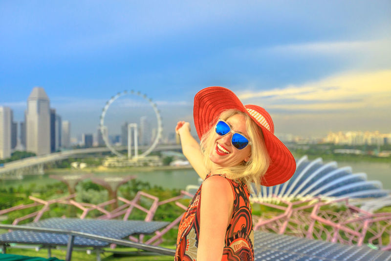 Happy lifestyle girl in wide hat showing the cityscape of Singapore city. Aerial view of Singapore marina. Travel holiday vacation in Singapore, Southeast Asia. Sunny day, blue sky. Singapore Singapore City Woman Tourist Tourist Attraction  Tourist Destination People Girl Females Aerial View Skyline Cityscape Panorama Happy Travel Hat Lifestyle Enjoy Nature Tourism Smiling One Person Sky Leisure Activity Architecture Lifestyles Young Women Water Built Structure Young Adult Real People Focus On Foreground Women Portrait Standing Clothing Building Exterior Waist Up Fashion Hair Hairstyle Outdoors Beautiful Woman