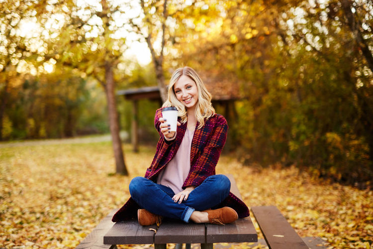 Adult Autumn Beautiful Woman Blond Hair Casual Clothing Change Day Happiness Leaf Leisure Activity Lifestyles Long Hair Looking At Camera Nature Outdoors Park - Man Made Space Portrait Real People Sitting Smiling Togetherness Tree Two People Young Adult Young Women