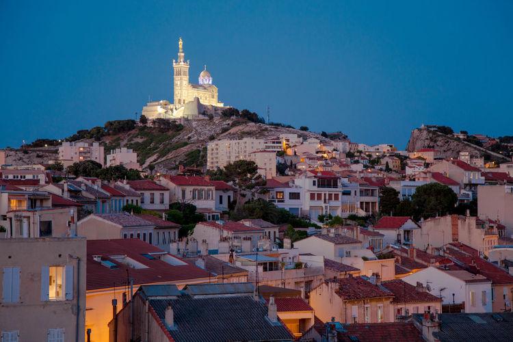 View of cityscape and notre-dame de la garde against clear blue sky