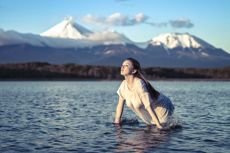Young woman looking away while standing in lake against snowcapped mountain