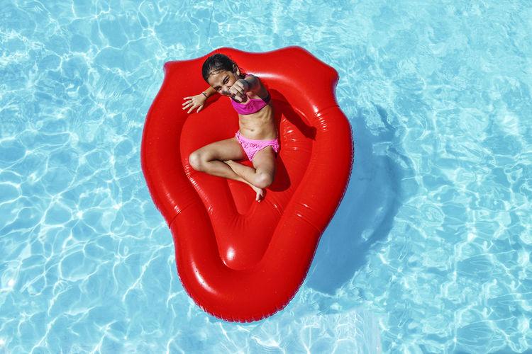 High angle view of young woman lying on swimming pool