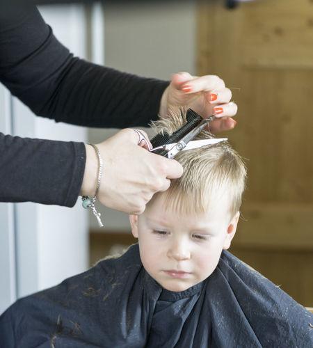 Boy getting haircut in barber shop