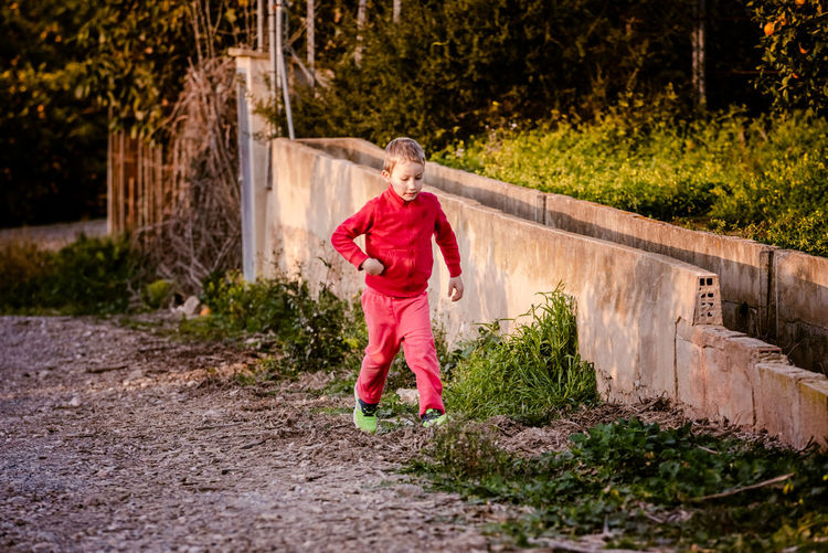 Boy walking on footpath by plants